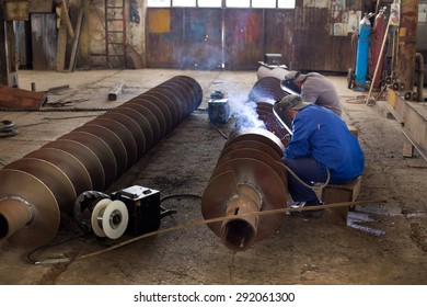 Two workers welding ship part in messy workshop