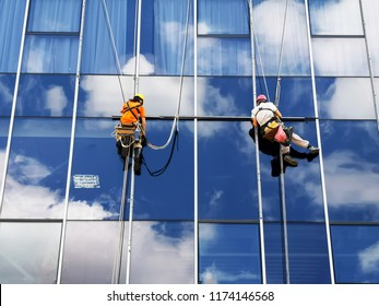 two working climbers are working on a glass wall of a high-rise building