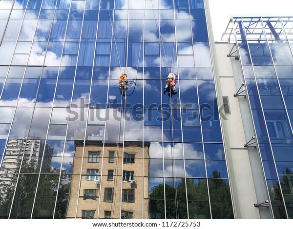 two working climbers on a glass wall of a high-rise building, bottom view
