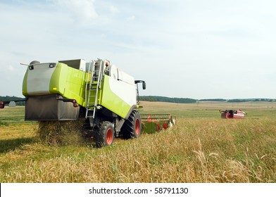 Two working harvesting combines in the summer field of wheat cereals