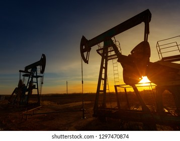 Two working oil pumps silhouette against sunset