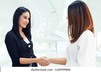 Two working women shaking hands after meeting business on bright background