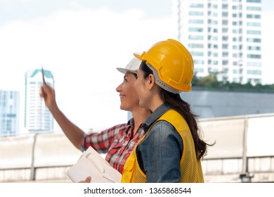Two working women are working together as team at constructional sit with building background