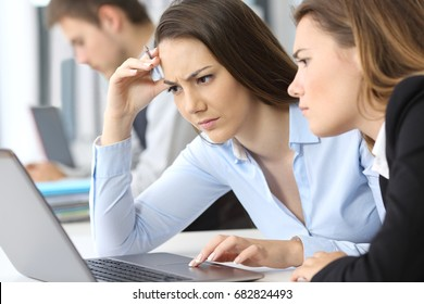 Two worried businesswomen working on line with a laptop at office