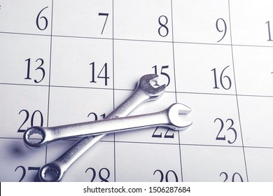 two wrenches lie on top of each other forming a cross. repair according to the schedule in the calendar, routine maintenance