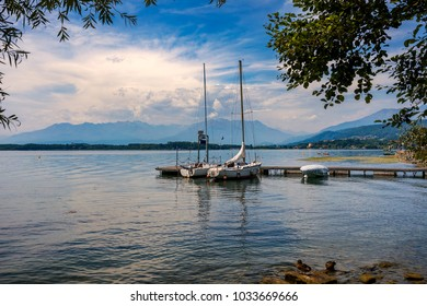 Two yachts moored at small wooden pier under beautiful sky on Lake Viverone in Piedmont, Northern Italy.