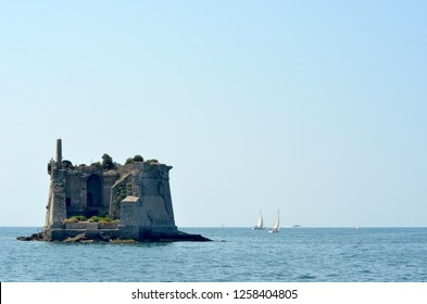 Two yachts are near a ruined tower on a small island. It is surrounded by a calm ocean. The tower has trees and shrubs growing on it. The sky is blue.