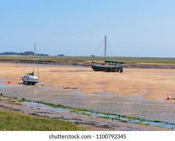 Two yachts, one old and one more modern, are beached on a sandbank at low tide in an estuary. Salt marches stretch out in to the distance