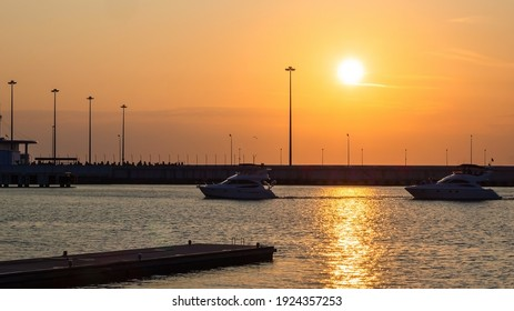 Two yachts sail along the pier on the sea illuminated by the glare of the setting sun