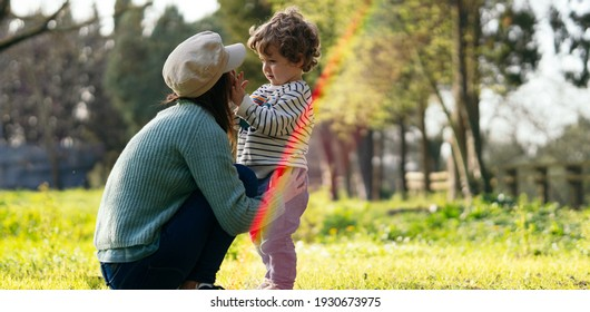 two year old boy with his mother on an afternoon in spring. family lifestyle concept. with lens flare