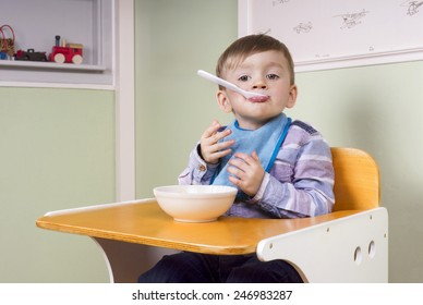 two year old boy sitting in his chair eating yogurt and acting silly