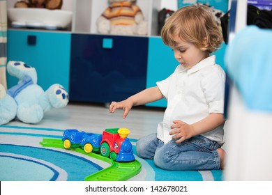 A two year old child playing in his room with a toy train