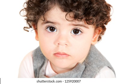 Two year old girl with curly hair portrait, studio shot.