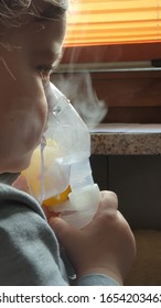 Two year old girl making inhalation with nebulizer at home