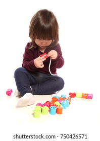 two year old girl playing with cotton reels in studio