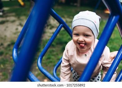 Two year old girl smiling and playing outside at playground