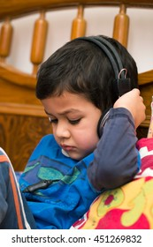 two year old indian kid listening the music through headphones