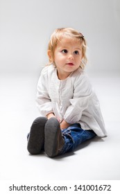 Two year old kid sitting in studio, shy.