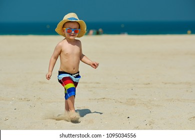Two year old toddler boy in sun hat running on beach