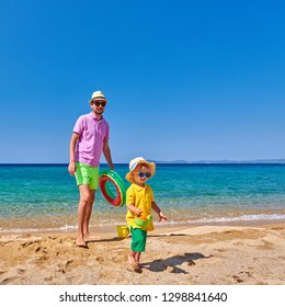 Two year old toddler boy walking on beach with father, holding inflatable ring. Summer family vacation. Sithonia, Greece.