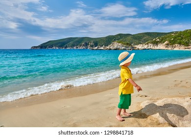 Two year old toddler boy walking on beach. Kid wearing straw sun hat. Summer family vacation. Sithonia, Greece