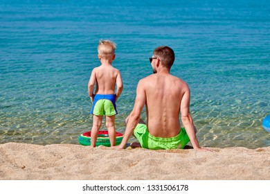 Two year old toddler boy on beach with father. Summer family vacation. Sithonia, Greece.