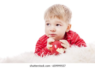 Two years Boy eating red apple isolated on white