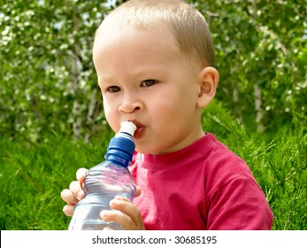 two years old boy drinking mineral water - resting in the forest