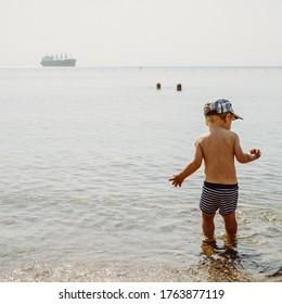 Two years old boy having fun in warm water of Red Sea.