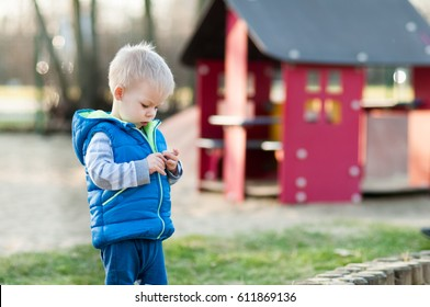 Two years old boy is looking at something on his hands. Playground on background.