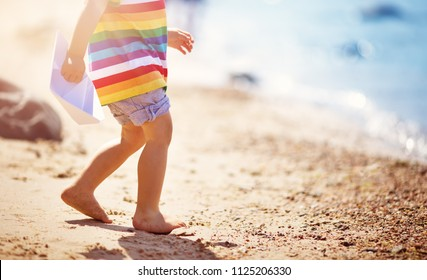 two years old boy playing at the beach in hat. Child with a paper ship at sea