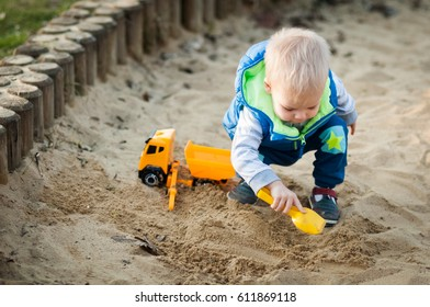 Two years old boy is playing in sandbox