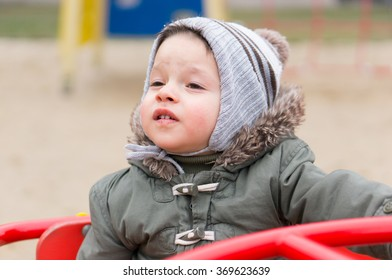Two years old child sitting in a play ground roundabout on a cold day