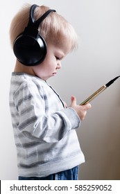 Two years old dissatisfied boy heeds in to the sounds of music in headphones, holding in hands the smartphone. Small critic