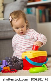 Two years old toddler girl playing on the floor, putting plastic shapes into the box with appropriate holes