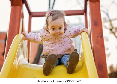 Two years old toddler girl playing on the yellow slider