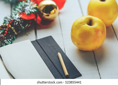 two yellow apples, notebook with pencil and Christmas decoration on white wood background
