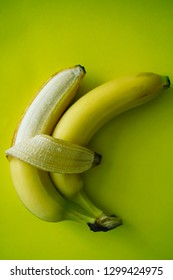 two yellow bananas isolated on green background. Love and tenderness. sign, symbol, concept of embracing couple