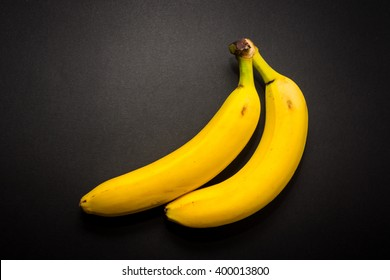 Two yellow bananas on the black background