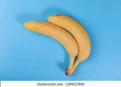 Two yellow bananas together on a blue background. The concept of non-traditional sexual relationships. The idea of two lovers having sex