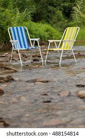 two yellow and blue chair put in stream rocky waterfall with green environment forest nature background.