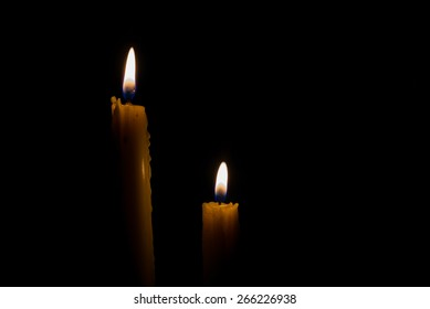 two yellow candle with dark background