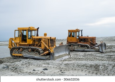 Two yellow caterpillar tractors