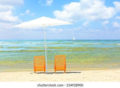 Two yellow chairs under a white umbrella on a sandy beach of Mediterranean sea