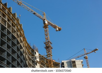 two yellow construction cranes running near the house under construction, the elements of the house frame and the crane
