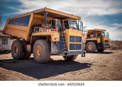 Two yellow dump trucks ready to work