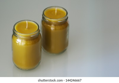 Two yellow homemade craft wax candles in glass jars.