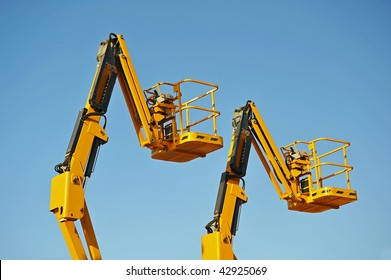 Two yellow hydraulic lift cherry pickers