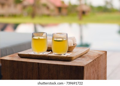 Two yellow lemonade glasses on a wooden tray and wood block next to a swimming pool in boutique hotel resort in Cambodia.