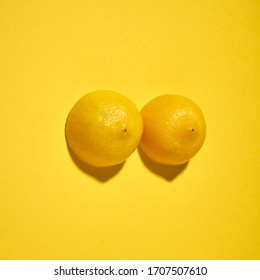 Two yellow lemons on a bright yellow background, imitation of a beautiful female breast.